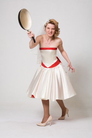 An angry bride waving a frying pan. Woman in wedding dress in full length on a white background in studio