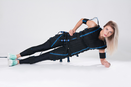 Blonde in an electric muscular suit for stimulation makes an exercise on the rug. Young woman in EMC suit isolated on white background