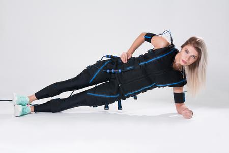 La bionda in un completo muscoloso elettrico per la stimolazione fa un esercizio sul tappeto. Giovane donna in tuta EMC isolato su sfondo bianco Archivio Fotografico - 90788436