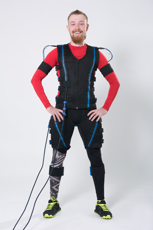 Red-haired man with a beard in electric muscular suit for stimulation. Male in a ems suit isolated on white background
