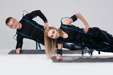 Young man and a woman in an electric muscular suit are trained to stimulate themselves. Fitness in EMC suit isolated on white background