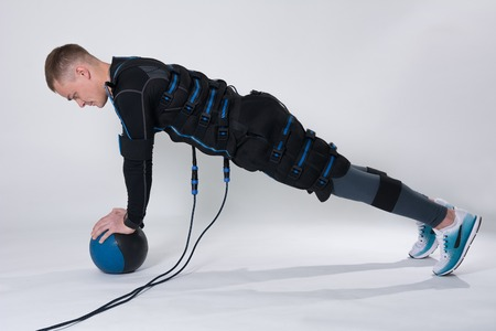 Fitness man in an electric stimulation suit on a white background in studio in full growth does exercise with the ball