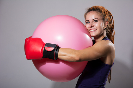 Young woman boxer with big rubber ball. Girl smiling with dreadlocks and in boxing gloves on gray background Stock Photo