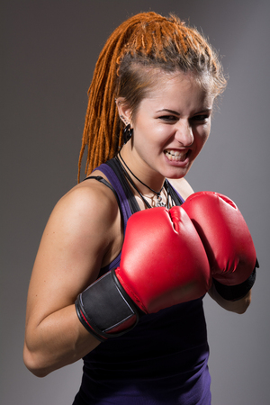 Young woman boxer with dreadlocks with clenched teeth. Girl with red boxing gloves on gray background looking at camera