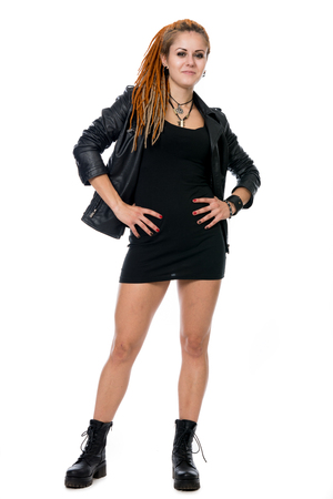 Young woman with dreadlocks in a leather jacket. A girl in a skirt and boots with full-length hands on the belt