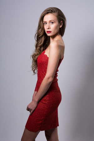 Portrait of a young woman in a red dress. Beautiful fashion woman on a gray background Stock Photo