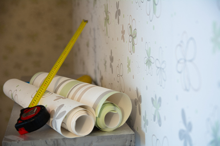 Two rolls of wallpaper and a measuring tape measure lie against the wall with floral wallpaper