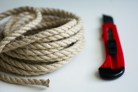 Coarse rope roll and a knife with a red handle on a white surface