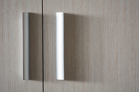 Background wooden texture door with plastic metallic handles.