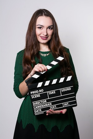 Young woman holding a movie clapper. Cheerful girl in green dress helps in shooting a movie