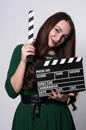 Young woman holding a movie clapper. Girl in green dress helps in shooting a movie 版權商用圖片