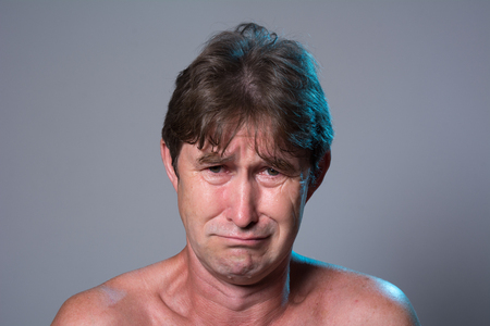 Close-up portrait of a sad man. Resentment of a man with a bare torso