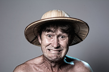 Close-up portrait of an embittered man with a naked torso in a hat on a gray background. A man in a straw hat shows teeth