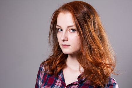 Portrait of a serious young woman in a plaid shirt. Lovely red-haired girl on a gray background
