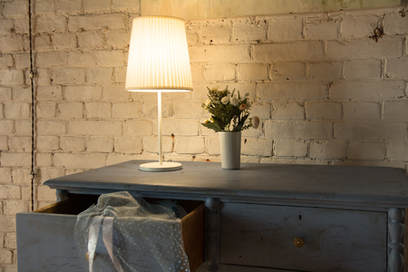 Lamp and bouquet with flowers on an old chest of drawers background of a brick wall Stock Photo