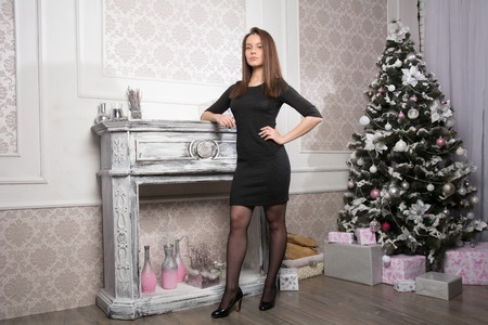 Young brunette in a black dress standing in full growth on the background of Christmas fir.