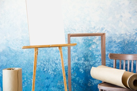 Easel background with a white sheet and a roll of paper for watercolors on a blue background.