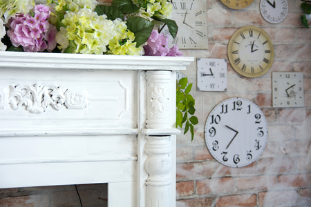 Decorative fireplace corner and wall background with clock and flowers.