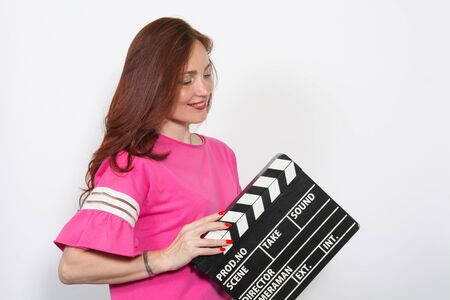 Woman in pink top with movie board isolated on white background