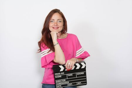 Redhead woman in pink top with movie board isolated on white background