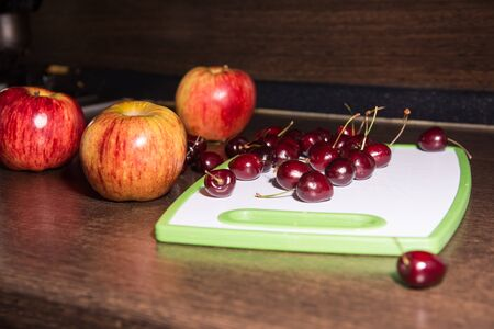 Background apples and cherries on a cutting board. Fruit on the kitchen table