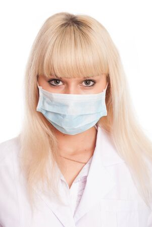 Close up of a young female nurse in mask looking at the camera. Doctor isolated on a white background Foto de archivo - 130489034