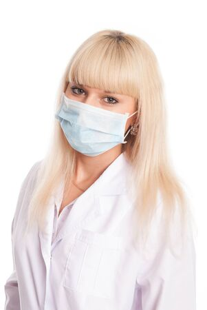 Close up of a young female nurse in mask looking at the camera. Doctor isolated on a white background