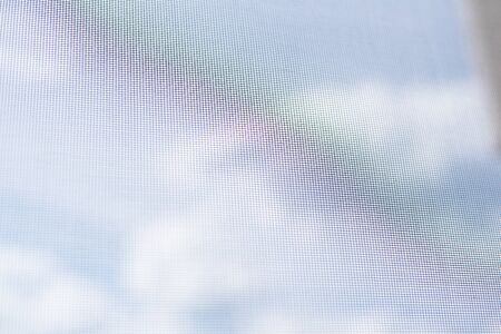 Background view from the window with a mosquito net on the sky with clouds and a rainbow. Virus isolation at home. Banque d'images