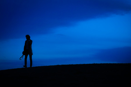Men silhouette standing on a hill