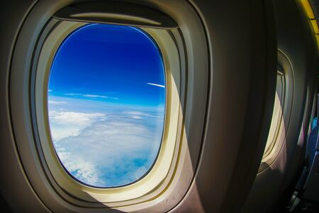 Clouds and sky visible from the window of an airplane Фото со стока