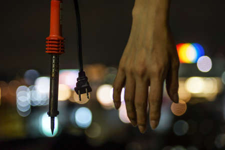 Soldering iron hands and urban night view