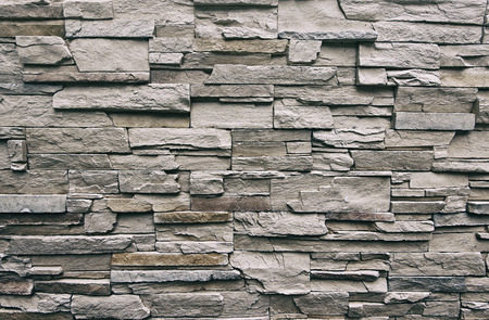 Close up of modern style design decorative uneven cracked real stone wall surface with cement, old vintage Foto de archivo