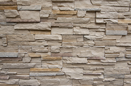 Close up of modern style design decorative uneven cracked real stone wall surface with cement photo