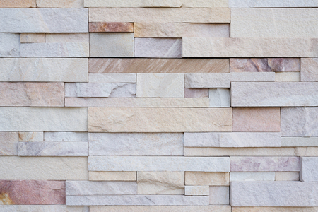 suface: Close up of modern style design decorative uneven cracked real stone wall surface with cement.