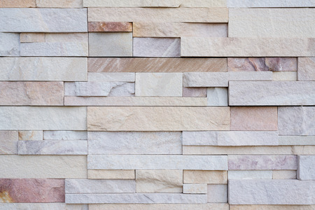 Close up of modern style design decorative uneven cracked real stone wall surface with cement.