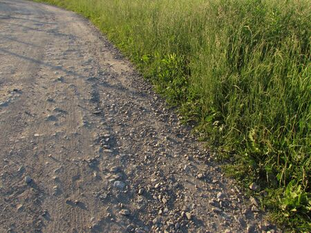 The edge of the roadside of a light rocky forest road and green summer grass in a corner