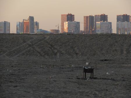A lonely black brazier on the gray sand of a beach with distant square town houses at dawn.