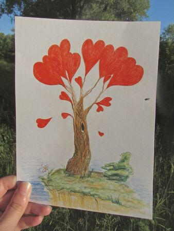 A hand is holding a drawing of a fantastic tree with red hearts, on which a bug sits, in the light of the rising sun against the background of the summer forest.