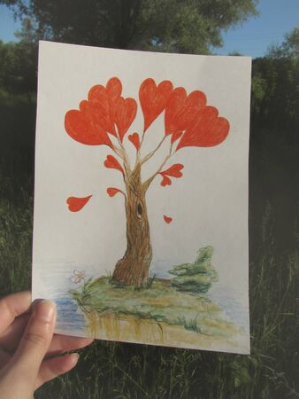 A hand is holding a drawing of a fantastic tree with red hearts in the light of the rising sun against the background of the summer forest.