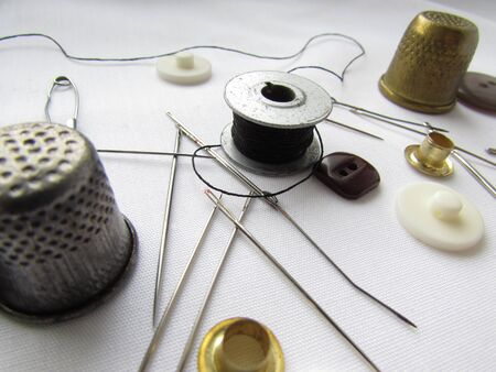 A set of needles, thimbles, buttons, pins, threads of black and red colors chaotically lying on a bright white background.