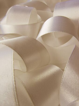 White crumpled brilliant light wedding milky color satin ribbon with bends and spirals background.