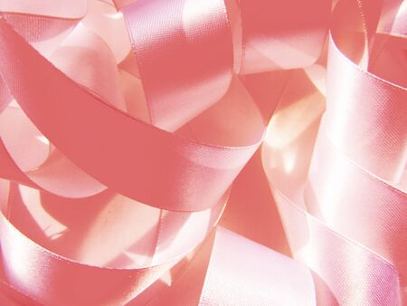 Wide pink sweet pastel color satin ribbon lying sewing chaotic rings gentle background.