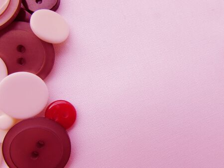 The composition of white, red and brown buttons on a light pink fabric background.