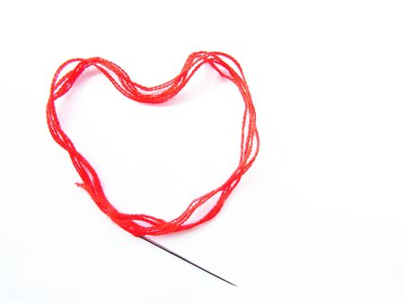Bright red scarlet wool thick thread with a sewing needle lies in the shape of a heart isolated object on a white background. Stock fotó
