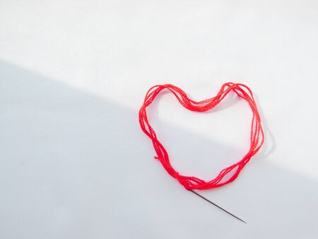 A bright red scarlet woolen thick thread with a sewing needle lies in the shape of a heart, lit on the left against a white background with a shadow.