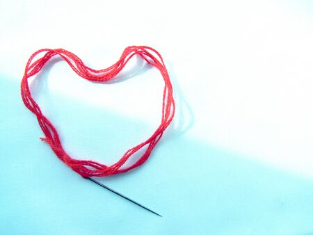 A bright red scarlet woolen thick thread with a sewing needle lies in the shape of a heart, lit on the left on a delicate white and blue background.