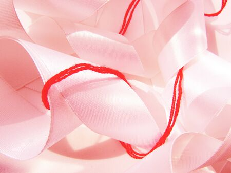Bright red scarlet wool thick thread wrapped around a light pink satin wide ribbon chaotic sewing background.