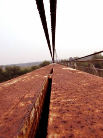 Old red iron stripes of the handrail, steel cables, construction of a metallic rusty bridge against the background of a distant landscape and sky.
