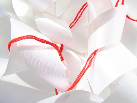 Bright red scarlet wool thick thread wrapped around a white milk satin wide ribbon chaotic sewing background. Banco de Imagens