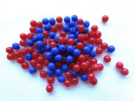 Bright red and deep dark blue round beads for needlework on a white background isolated object. Imagens